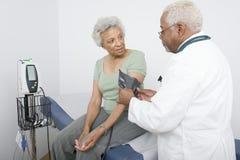 Measuring Patient医生的在诊所的血压 库存照片