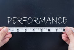 Measuring performance. Tape measurement of the word performance on a chalkboard Stock Image