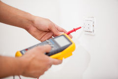 Measuring power from an outlet. Closeup of a man using a multimeter to measure the output of a power outlet stock photos