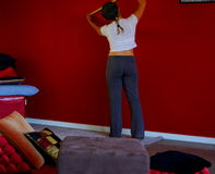 Measuring A Red Wall. Photograph taken inside a modern house featuring a woman measuring part of a red feature wall, surrounded by cushions (Adelaide, Australia royalty free stock photos