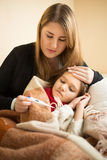Measuring sick daughter temperature with digital thermometer Stock Image