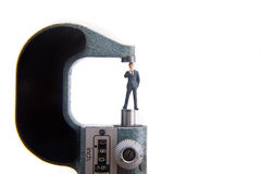 Measuring Small Business. Miniature business man with micrometer Royalty Free Stock Photography