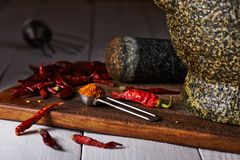 Measuring spoon with ground pepper on a chopping board, dried peppers. Stone mortar and pestle royalty free stock image