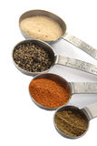 Measuring Spoons full of Spices. One Tablespoon, One Teaspoon, Half Teaspoon and Quarter Teaspoon measuring spoons filled with colorful spices isolated on a Stock Photos