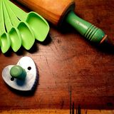 Measuring spoons, heart cookie cutter and antique wood rolling pin with painted green handle Royalty Free Stock Images