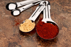 Measuring spoons with red and yellow spices Royalty Free Stock Photography