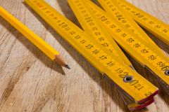 Measuring Stck and Pencil on a Wooden Table. A yellow measuring stick and a pencil on an old wooden table Stock Images