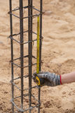 Measuring steel rod at construction site with tape measure Royalty Free Stock Photography