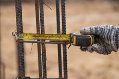 Measuring steel rod at construction site with tape measure Royalty Free Stock Images