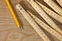 Measuring Stick and Pencil on a Wooden Table. A measuring stick and a pencil on an old wooden table Stock Photography