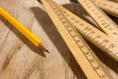 Measuring Stck and Pencil on a Wooden Table. A measuring stick and a pencil on an old wooden table Royalty Free Stock Photo