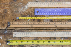 Measuring sticks, rulers, tape measures on workshop table in lin Royalty Free Stock Photography