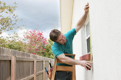 Measuring For Storm Shutters. A carpenter measuring a window for hurricane shutters.  Dark storm clouds are overhead Stock Image