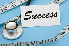 Measuring Success. A white measuring tape with a note saying success on a blue background, measuring success Royalty Free Stock Photo
