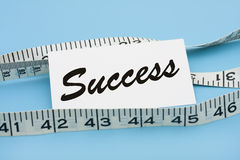 Measuring Success. A white measuring tape with a note saying success on a blue background, measuring success Stock Image