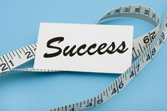 Measuring Success. A white measuring tape with a note saying success on a blue background, measuring success Royalty Free Stock Photos