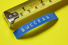 Measuring success. Measurement of success concept - tape measure against a label reading success Royalty Free Stock Photography
