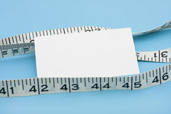 Measuring Success. A white measuring tape with a blank note on a blue background, measuring success Royalty Free Stock Images