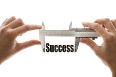 Measuring success. Close up shot of a caliper measuring the word Success Royalty Free Stock Photo