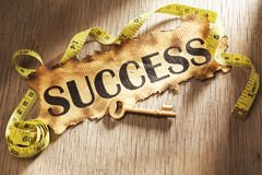 Measuring success concept. Using burnt paper with word success printed on it and golden key surrounded by measuring tape Stock Photography