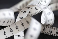 Measuring tailor tape. Closeup, macro. On numbers, industrial concept Royalty Free Stock Images