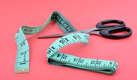 Measuring tape. With scissors in red background Royalty Free Stock Photos