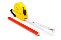 Measuring tape. A metal measuring tape and a pencil Royalty Free Stock Photo