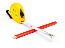 Measuring tape. A metal measuring tape and a pencil Royalty Free Stock Images