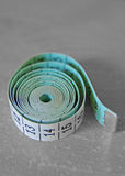 Measuring tape. Rolled up measuring tape on grey background Royalty Free Stock Images