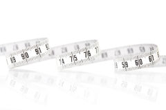 Measuring tape. And its reflection on white background Royalty Free Stock Photography