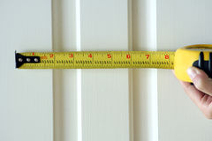 Measuring Tape. A person measure a section of the wall with this yellow measuring tape Royalty Free Stock Photo
