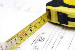 Measuring tape. Carpenters measuring tape on backgrouond of home renovation plans stock image