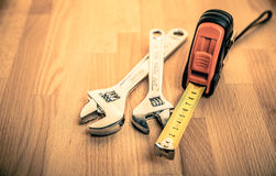 Measuring tape and Adjustable Wrenches on table Stock Photos