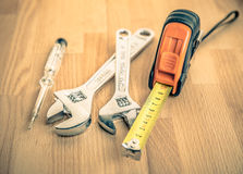 Measuring tape and Adjustable Wrenches on table Royalty Free Stock Image