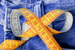 Measuring tape against the backdrop of jeans Stock Images