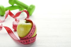 Measuring tape with apple and dumbbells Stock Photography