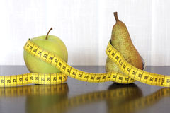 Measuring tape, apple and pear royalty free stock photography