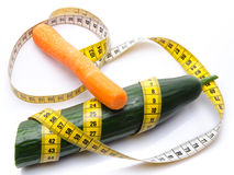 Measuring tape around a cucumber with a carrot Royalty Free Stock Photos