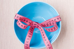 Measuring tape around empty bowl on table Royalty Free Stock Images