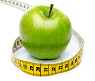 Measuring tape around a green apple Stock Image