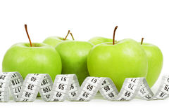 Measuring tape around a green apples as a symbol of diet. Royalty Free Stock Photo
