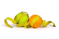 Measuring tape around the orange and green apple. Stock Photo