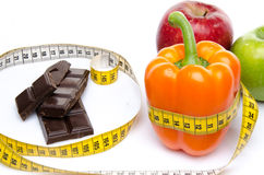 Measuring tape around a pepper and chocolate with apples Royalty Free Stock Photography