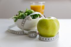 Free Measuring Tape Around The Apple, Bowl Of Green Salad And Glass Of Juice. Weight Loss And Right Nutrition Concept Stock Photo - 111909710