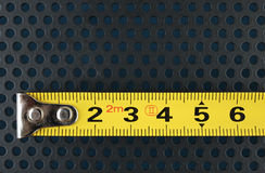 Measuring tape on a background with perforation of round holes. Measuring tape on a metallic background with perforation of round holes Royalty Free Stock Image