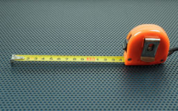 Measuring tape on a  background with perforation of round holes. Measuring tape on a metallic background with perforation of round holes Stock Photo