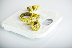 Measuring tape on bathroom scales Royalty Free Stock Photos