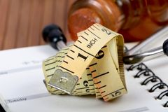 Measuring tape. Beautiful shot of rolled measuring tape on diary Royalty Free Stock Images