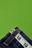 Measuring tape belt. Measuring tape threaded through belt loops of denim jeans Royalty Free Stock Photos