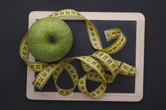 Measuring tape on blackboard with green apple Royalty Free Stock Photos